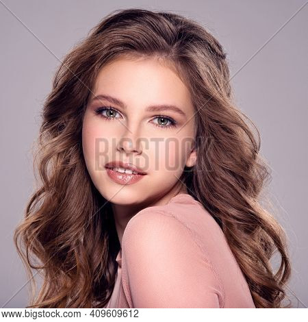 Beautiful brown-hair girl with long, wavy hair. Young fashion model posing in the studio. Happy caucasian girl looking and smiling at camera. Attractive woman with makeup looking at the camera.