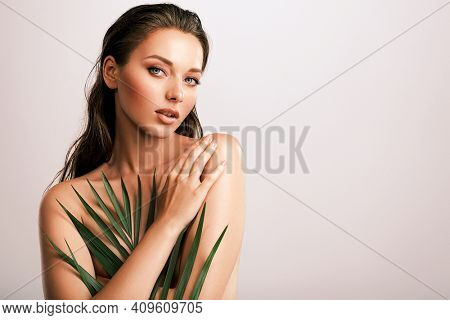 White woman with healthy skin of body and palm leaves. Tanned body of an attractive girl with green plants. Large palm leaves cover the body.