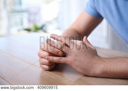 Man Taking Off Wedding Ring At Wooden Table Indoors, Closeup. Divorce Concept