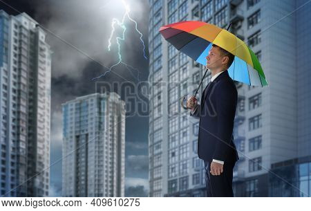 Businessman With Umbrella In City Center. Insurance Concept