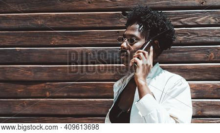 Profile Portrait Of A Young Stylish Black Female Talking On The Phone In Front Of A Wooden Surface;