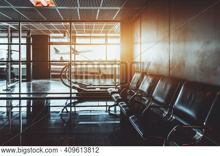 View Of An Airport Waiting Room With The Row Of Empty Seats In The Foreground, An Escalator Or A Tra
