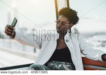 Portrait Of A Beautiful Young African Woman In A White Trench And Elegant Sunglasses Sitting In A Ca