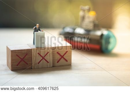 Miniature People Politician Stand On Podium With Symbol X During A Public Speaking And With Blur Of