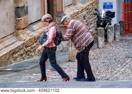 Bergamo, Italy - May 22, 2019: Unknown Elderly Man And Woman Crossing The Road In Bergamo.