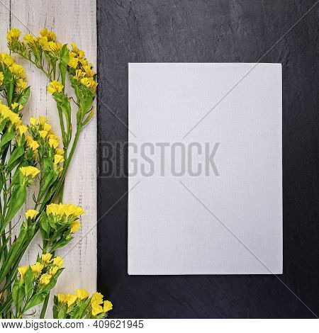 Blank White Card Decorated With Yellow Statice Flowers On Black Slate And White Wooden Background. M
