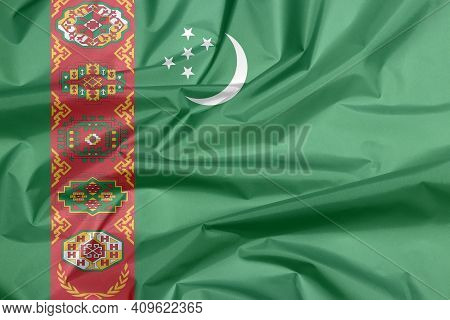 Fabric Flag Of Turkmenistan. Crease Of Turkmen Flag Background, Green Field With Red Stripe Containi