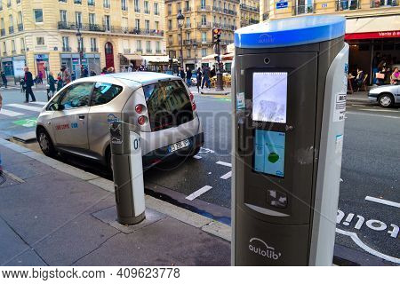 Paris, France, January 6, 2016. Electric Car At Charging Station With The Power Cable Supply Plugged