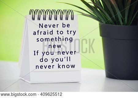 Inspirational Quote On White Paper Stand With Potted Plant And Blurred Background - Never Be Afraid