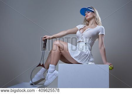 Relaxed Hot Girl With Cap And Blond Hairs Dressed In White Shirt And Skirt Sits On Box In White Back