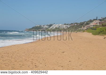 Golden Sandy Beach With Sea And Residential Buildings