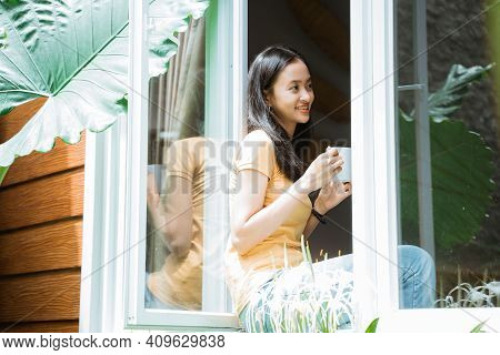 Beautiful Woman Drinking Coffee In The Morning By The Window. View From Outside.