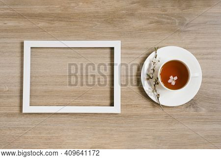 A White Cup With Black Tea And A Sprig Of Apple Blossom And A White Frame On A Wooden Background. Mo