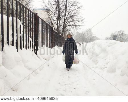 Older Mature Woman Carries Shopping Bags In A Heavy Snowfall. Middle Aged Grandmother Walking In A B