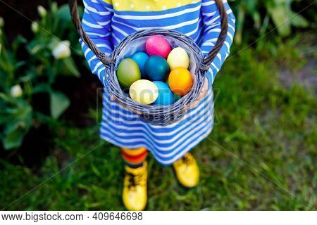 Close-up Of Of Hands Of Toddler Holding Basket With Colored Eggs. Child Having Fun With Traditional