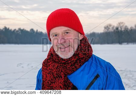 Elderly Man In Red Knitted Hat And Scarf Standing In Winter Forest, Resting After Exercise And Looki