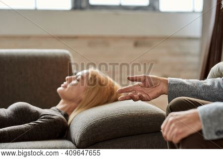 Psychoanalyst Talking To Calm Young Caucasian Woman Lying On Sofa With Closed Eyes During Appointmen