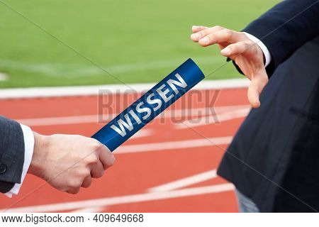 Businessmen Passing Baton In Relay Race With German Word Wissen Means Knowledge