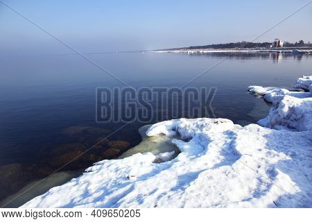 Unusually Calm Baltic Sea With Ice On The Shore On A Winter Sunny Day In Riga, Latvia