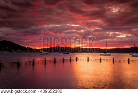 Red Sunset Over The Estuary Waters At Yattalunga With Fenced Pool. Boats Moored In The Distance Bob