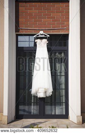Amazing Wedding Dress Hanging On Hanger Outdoors