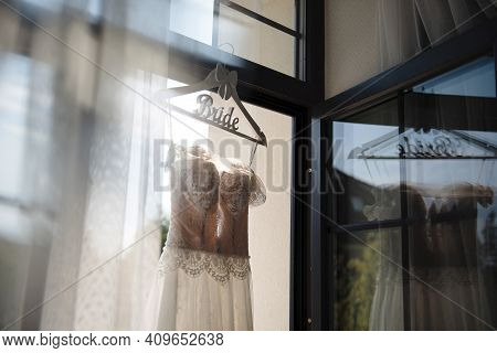 Close Up Of Hanger With Wedding Dress For Bride