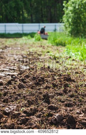 A Man On A Track Cultivator Digs A Private Plot. Focus On The Foreground On Clods Of Earth