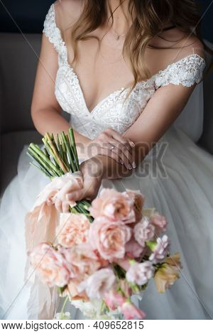 Close Up Of Charming Bride In Wedding Dress Holding Bouquet