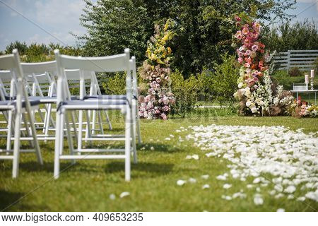 Open Air Wedding Ceremony With Arch And Chairs