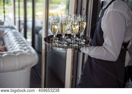 Close Up Of Waiter Carrying Tray With Glasses Of Champagne