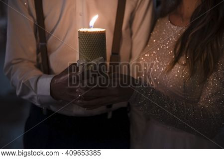 Close Up Of Groom And Bride Holding One Burning Candle