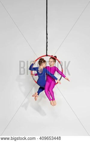 Two Little Child Girls Shows An Acrobatic Performance On An Aerial Hoop. Aerial Acrobat