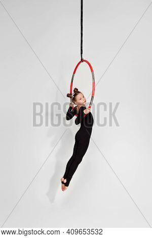 Little Acrobat Girl Shows An Acrobatic Performance On An Aerial Hoop
