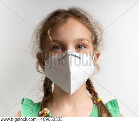 Infection Concept. Portrait Of Little Blonde Girl Wearing Medical Mask, Grey Background