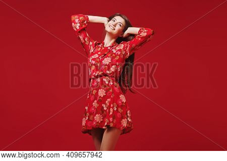 Portrait of a gorgeous smiling young woman in light red dress with flowers on a red background. Beauty and fashion. Make-up and hair.