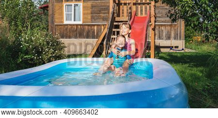 Staycation At Home. Little Girls,kids In Swimsuit Rolls Down Slide Into Inflatable Rubber Pool. Swim