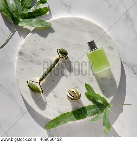 Jade Face Roller For Facial Massage Therapy, Essential Oil Glass Bottle. Top View On Round Marble Po