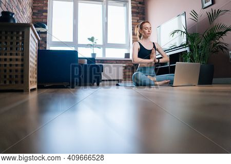 Remote View Of Relaxed Redhead Young Woman Wearing Sportswear Is Meditating In Lotus Position Sittin