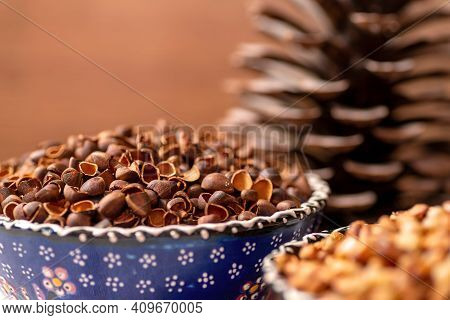 A Large, Open Pine Cone Next To The Ceramic Bowls. They Contain Pine Nuts, Shells And Peeled Nuts. C