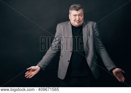 Clueless Indifferent Hesitating Man Shrugging Hands On Black Studio Background. No Idea, Fail, Doubt