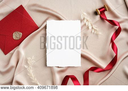 Elegant Wedding Stationery Set Top View. Flat Lay Blank Invitation Card Mockup, Red Ribbon, Envelope