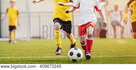 Group Of Children Playing Sports. Kids Kicking Soccer Ball. Football Tournament For School Kids. You