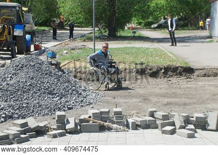 A Man In A Wheelchair On A City Street Under Repair. Dismantling Of Asphalt And Laying Paving Slabs.