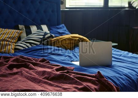 The Laptop Is On The Bed. The Concept Of Working At Home