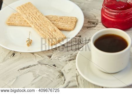 Crispbread With Jam For Breakfast On A Gray Background. A Jar Of Fresh Honey With Foam Is Next To A