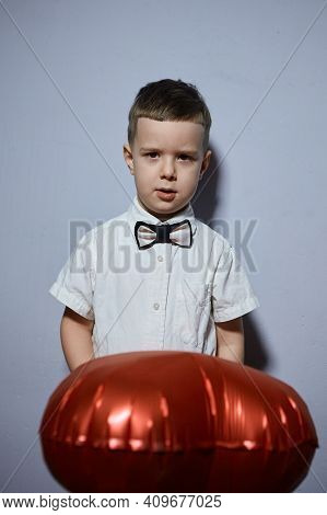 Valentine's day. Happy boy stands and holds red ball hearts on a white background.