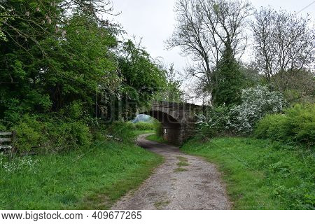 Dirt Pathway Passing Under A Curved Bridge In England.