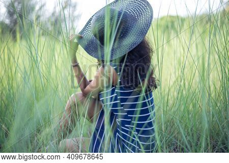 A girl with a stylish hat sitting lonely and enjoying nature in the grassland. Beautiful and serene photo of a nature-loving people.