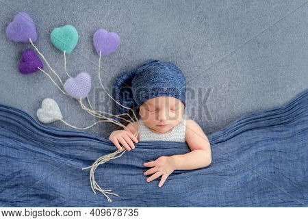 Concept newborn baby boy studio photoshoot. Infant sleeping covered with a blue blanket and holding knitted toys in the shape of hearts