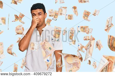 Young arab man wearing casual clothes smelling something stinky and disgusting, intolerable smell, holding breath with fingers on nose. bad smell